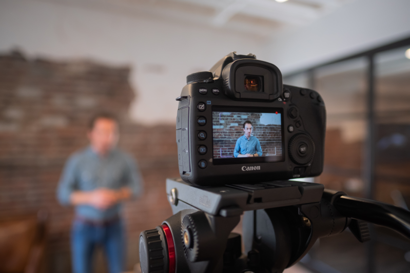 Man speaking for a webinar being filmed by a camera