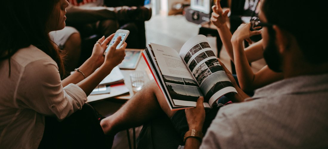 A group of people sat around a tabel reading different types of media